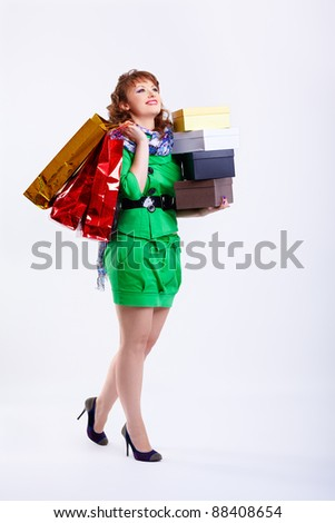 full-length portrait of happy young shopaholic woman walking with shopping bags and boxes on gray