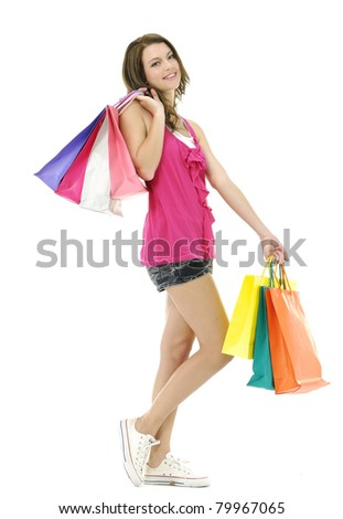Full length portrait of happy young woman carrying shopping bags - stock photo