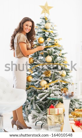 Full length portrait of happy young woman decorating christmas tree with christmas ball - stock photo