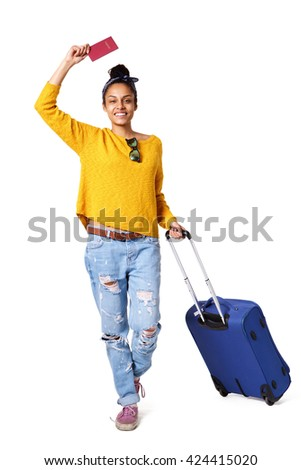 Full length portrait of happy young woman going on vacation with passport and her suitcase over a white background - stock photo
