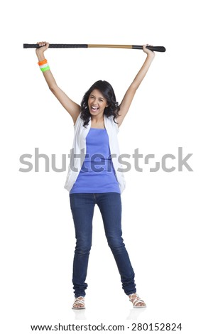 Full length portrait of happy young woman in casuals holding up hockey stick over white background - stock photo