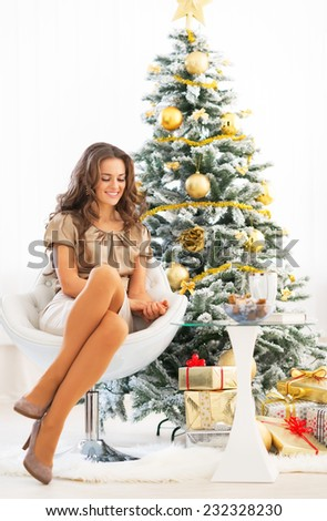 Full length portrait of happy young woman sitting near christmas tree - stock photo
