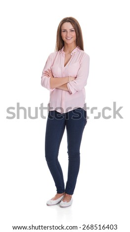 Full length portrait of happy young woman standing arms crossed over white background