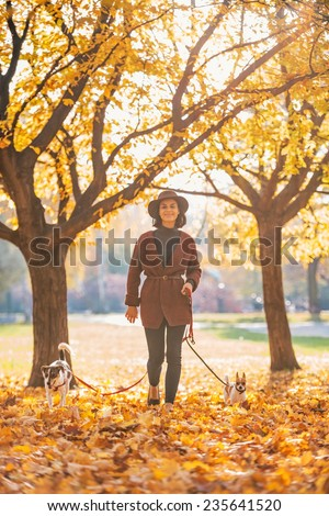 Full length portrait of happy young woman walking with dogs outdoors in autumn - stock photo