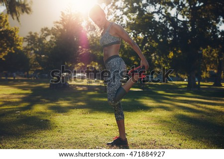 Full length portrait of healthy young woman working out in a park. Sportswoman warming up before training session outdoors on a sunny day.