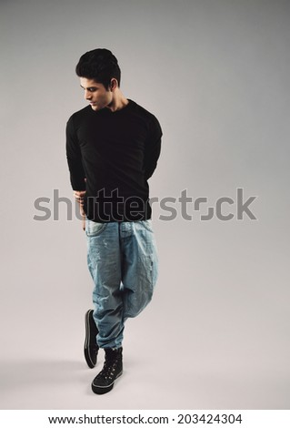 Full length portrait of hispanic young man in casuals posing. Male model looking down while standing on grey background. - stock photo