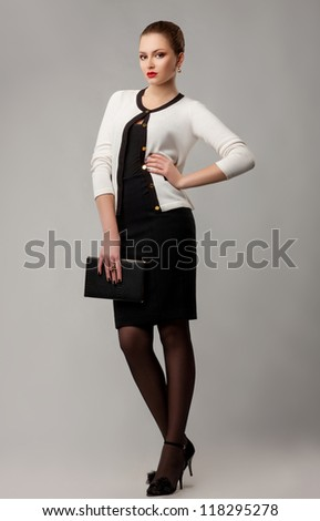 Full length portrait of intelligent young modern woman with book - stock photo