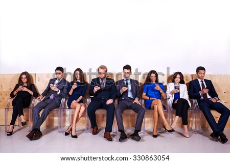 Full length portrait of International people dressed in corporate clothes using cell telephones while waiting for start interview, young intelligent lawyers chatting on smart phones during work break - stock photo