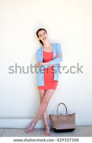 Full length portrait of laughing young woman with arms crossed - stock photo