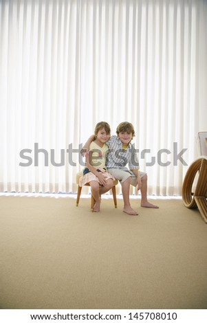 Full length portrait of little brother and sister sitting on stool in front of curtains - stock photo