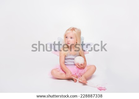 Full-length portrait of little fair-haired lovely girl wearing pretty grey vest and pink skirt sitting holding her magic wand and ball looking for someone. Isolated on white background - stock photo