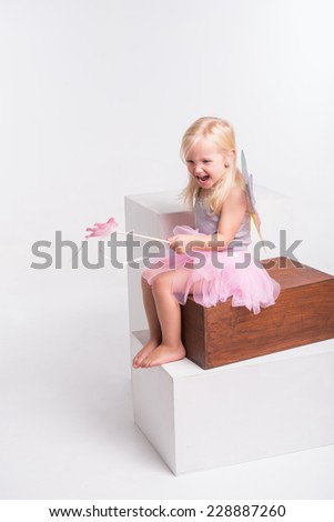 Full-length portrait of little fair-haired lovely smiling girl wearing pretty grey vest pink skirt and white wings holding a magic wand sitting on the wooden chair crying. Isolated on white background - stock photo