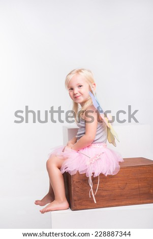 Full-length portrait of little fair-haired lovely smiling girl wearing pretty grey vest pink skirt and white wings holding a magic wand sitting on the wooden chair. Isolated on white background - stock photo