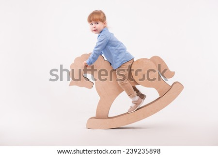 Full-length portrait of little lovely smiling girl wearing blue shirt and brown pants swaying on the wooden toy horse. Isolated on the white background - stock photo