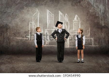Full-length portrait of little student in academic cap with friends against city drawing. Concept of graduation and future plans - stock photo