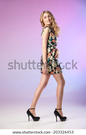 Full-length portrait of lovely woman in romantic dress on purple background