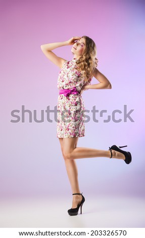 Full-length portrait of lovely woman in romantic dress on purple background - stock photo