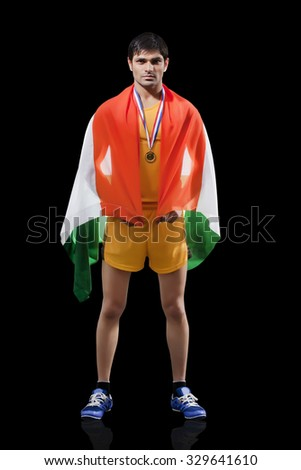 Full length portrait of male medalist with Indian flag standing against black background - stock photo