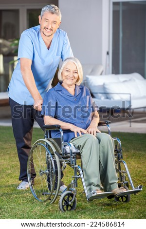 Full length portrait of male nurse standing with senior woman on wheelchair at nursing home lawn - stock photo