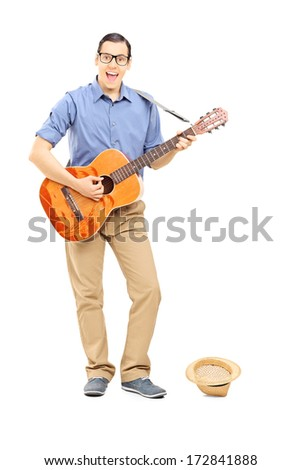 Full length portrait of male street musician playing guitar collecting money in hat isolated on white background - stock photo