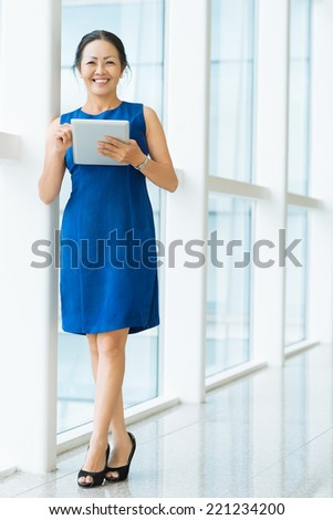 Full-length portrait of mature business woman holding a digital tablet - stock photo