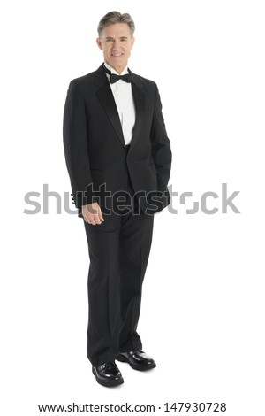 Full length portrait of mature man wearing tuxedo smiling while standing against white background - stock photo