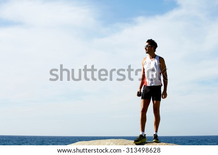 Full length portrait of mature sport man having rest after run while standing on the rock and listening to music in headphones, male runner taking break after active training outdoors in mountains - stock photo