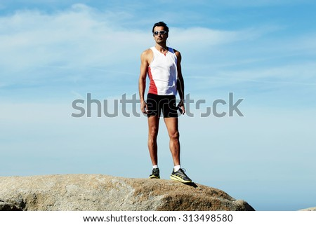 Full length portrait of mature sports man in workout wear standing on the hill of mountain rock while taking break after active fitness training, adult male runner resting after workout outdoors - stock photo