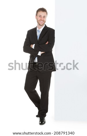 Full length portrait of mid adult businessman leaning over white background - stock photo