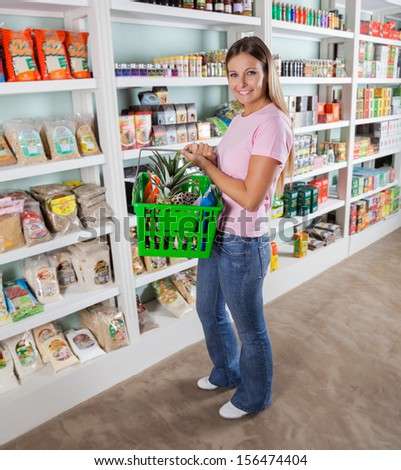 Full length portrait of mid adult woman carrying shopping basket in supermarket - stock photo