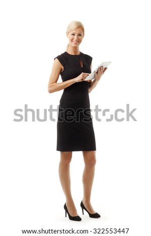 Full length portrait of middle age businesswoman standing against white background while working on digital tablet.