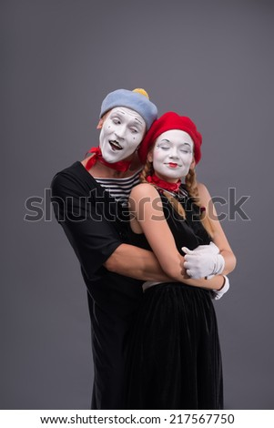 Full-length portrait of mime couple hugging with love each other, female mime closing her eyes, male mime looking at his girlfriend isolated on grey background with copy place - stock photo
