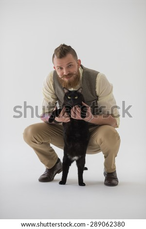 Full length portrait of modern groom posing with his cat - stock photo