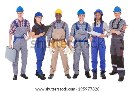 Full length portrait of multiethnic engineers standing against white background - stock photo