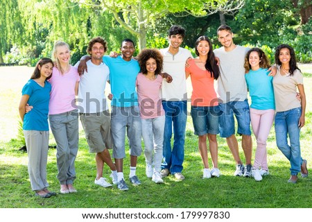 Full length portrait of multiethnic friends standing with arms around in park - stock photo