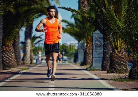 Full length portrait of muscular build athletic man jogging at sunny afternoon outdoors, handsome male jogger running down lane with palm trees on the sides and copy space area for your text message - stock photo