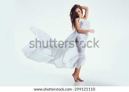 Full length portrait of naked woman with a sheer fabric on her body looking down. Sensuous female model posing over white background. - stock photo