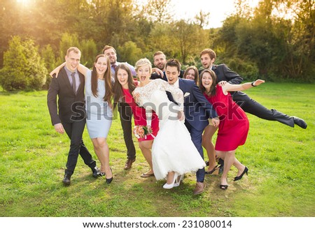 Full length portrait of newlywed couple having fun with bridesmaids and groomsmen in green sunny park - stock photo