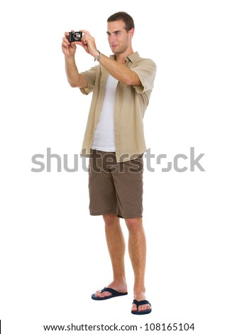Full length portrait of on vacation man in shorts pointing on copy space