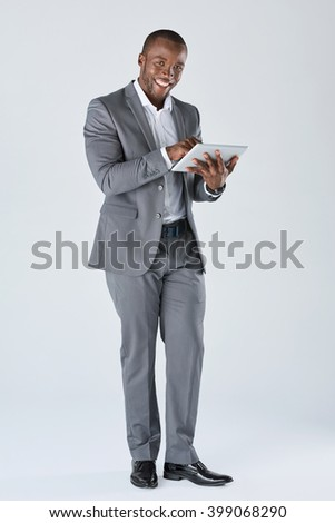 Full length portrait of positive friendly black  professional businessman with touchscreen tablet device in business suit isolated in studio - stock photo