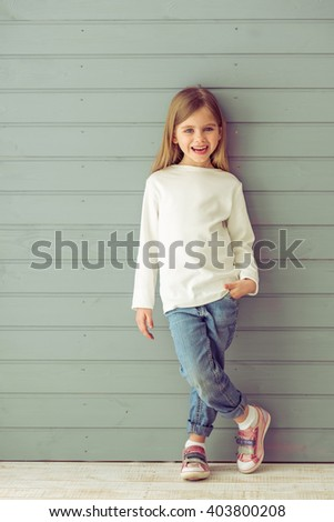 Full length portrait of pretty little girl in casual clothes looking at camera and smiling, standing against gray background - stock photo