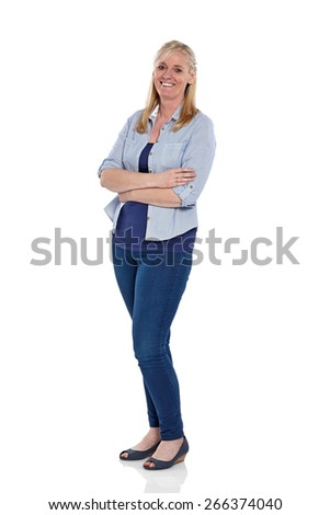 Full length portrait of pretty mature woman standing with her arms crossed on white background - stock photo