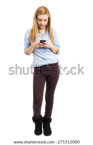 Full length portrait of pretty teenage girl using her smart phone over white background - stock photo