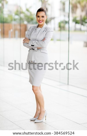 full length portrait of pretty young businesswoman with arms folded - stock photo