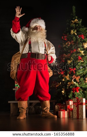 Full length portrait of Real Santa Claus carrying big bag full of gifts, at home near Christmas Tree - stock photo