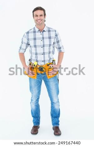 Full length portrait of repairman with tool belt around waist standing over white background - stock photo