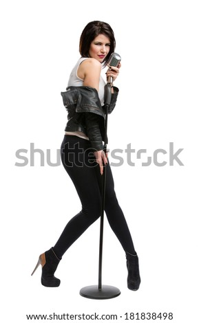 Full-length portrait of rock musician wearing leather jacket and keeping static mic, isolated on white. Concept of rock music and rave - stock photo