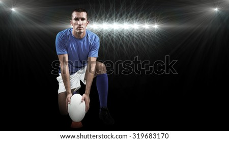 Full length portrait of rugby player placing ball against spotlight