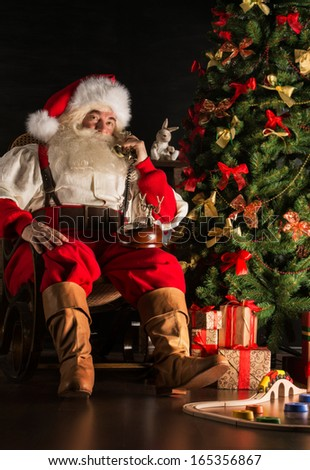 Full length portrait of Santa Claus calling by vintage phone. Sitting near Christmas tree at home