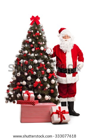 Full length portrait of Santa Claus standing next to a Christmas tree and looking at the camera isolated on white background - stock photo